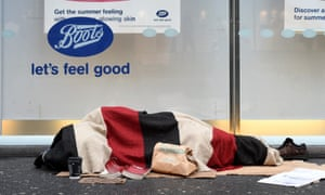 A homeless man sleeps outside of a shop in Oxford Street, London