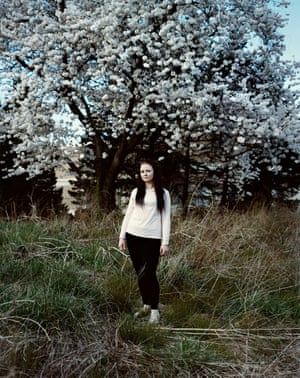 Woman stands wistfully under a tree in bloom