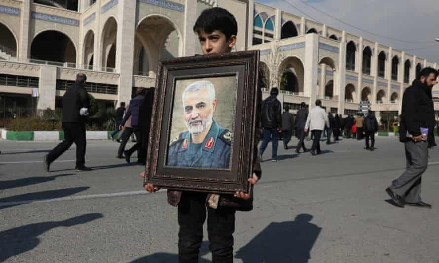 A boy in Tehran holds a portrait of Qassem Soleimani.