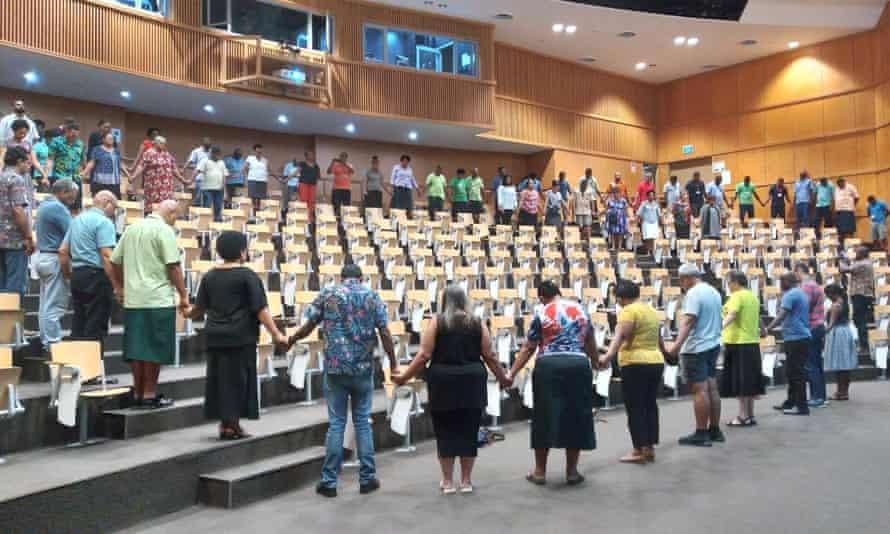 Staff at the University of the South Pacific Laucala campus in Suva, Fiji, stand together in. prayer for their deported vice-chancellor, Professor Pal Ahluwalia and his wife, Sandra Price.
