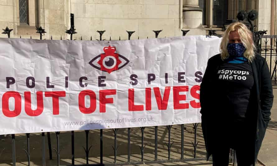 Kate Wilson next to a banner that says 'police spies out of lives' outside the Royal Courts of Justice in London