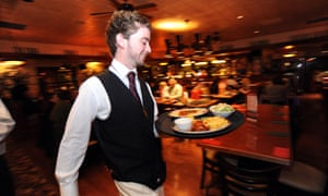 A waiter rushes with a tray of food in a busy restaurant