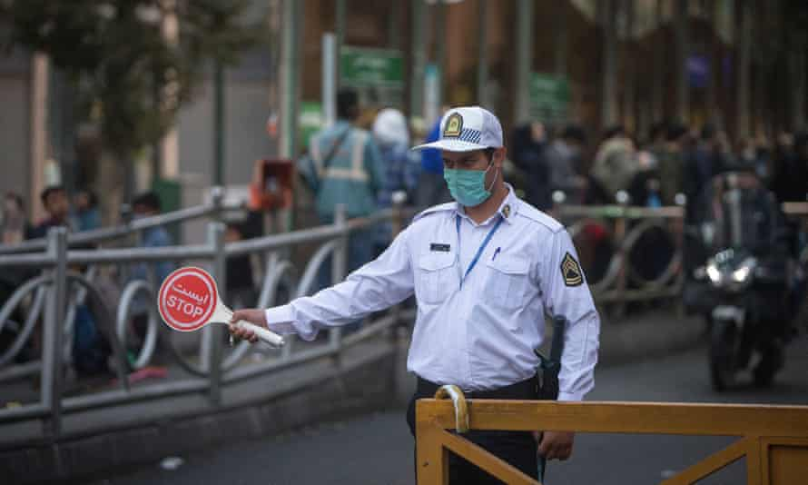 A police officer wearing a face mask works on a street in Tehran, Iran.