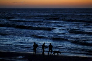 People walk with a dog on the beach after sunset at the Polish Baltic Sea coast near Choczewo.