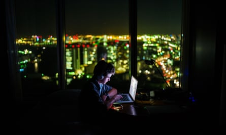 lonely teenage boy on laptop in dark room with bright city lights outside