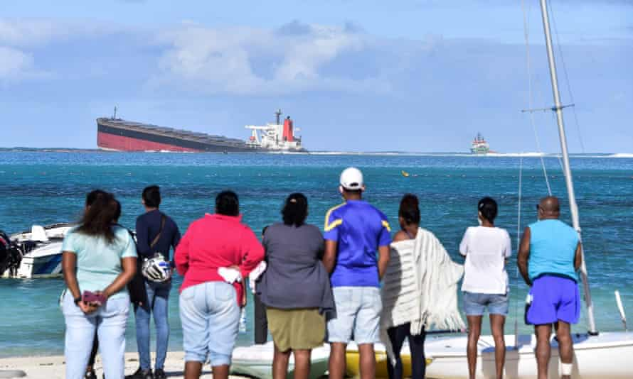 People gather to look at the stranded MV Wakashio ship which is leaking oil.