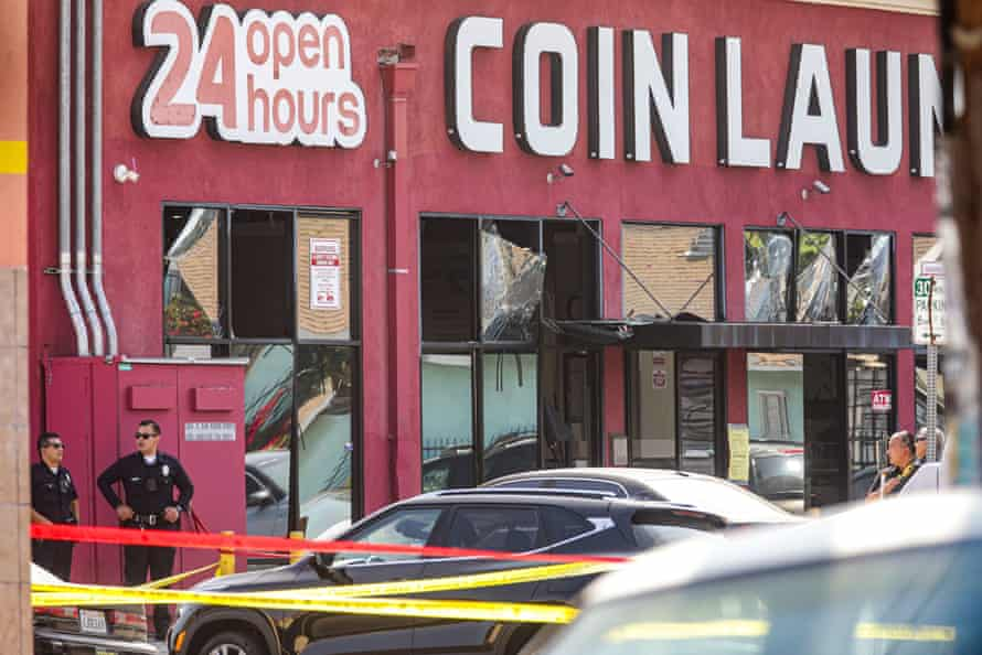 """Two police officers stand outside a red building with a sign reading """"Coin Laundry"""" that has several shattered windows."""