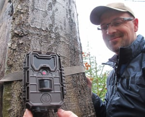 Robert Mysłajek fixes a motion-activated camera to a tree in Beskidy forest.
