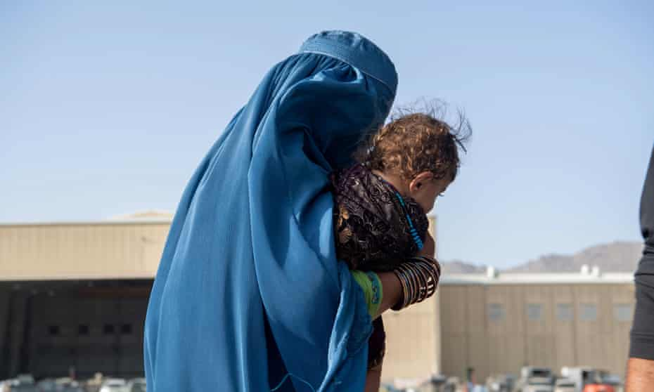 A woman carries a child on to an evacuation flight at Hamid Karzai International Airport in Kabul.