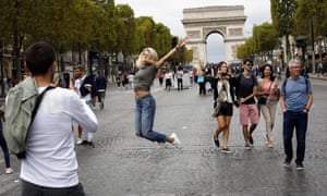 A woman jumps for a picture on the champs Elysees avenue, during the 'day without cars', with the Arc de Triomphe in background in Paris