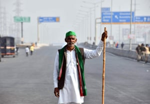 A farmer protests on the blocked highway at the Delhi-Uttar Pradesh border. The farmers fear the government will stop buying grain at minimum guaranteed prices and corporations will then push prices down. The government says it is willing to pledge that guaranteed prices will continue.