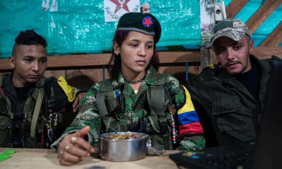 Guerrilla fighters watch as movie on a laptop.