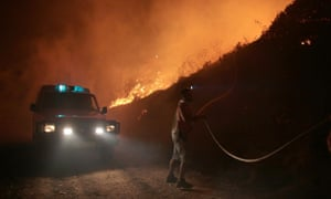 A firefighter tries to extinguish a forest fire in the Serra de Bouro district of Leiria, north of Lisbon, Portugal.