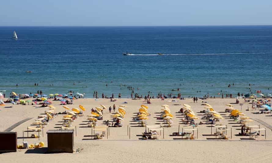Beachgoers sunbathe and swim at a beach in Portimao, Portugal.