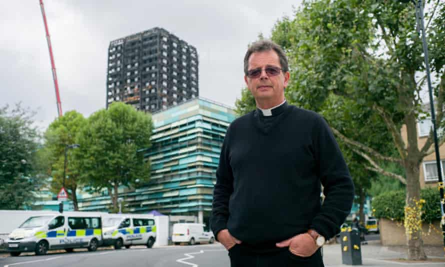 Father Alan Everett, vicar of St Clement, in front of Grenfell Tower.