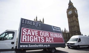 A van with a sign calling on the British government to 'Save Our Human Rights Act' drives past the Houses of Parliament in central London on May 27, 2015.