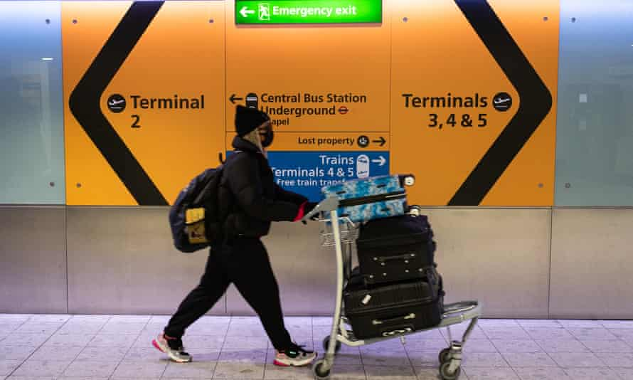 A woman wearing a protective face mask prepares to board a flight at Heathrow airport in London.