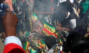 Supporters of the opposition MDC burn an election banner bearing the face of Emmerson Mnangagwa in Harare.