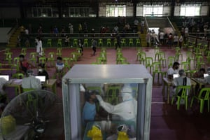 A health worker performs a Covid-19 swab test at a gymnasium in Navotas.