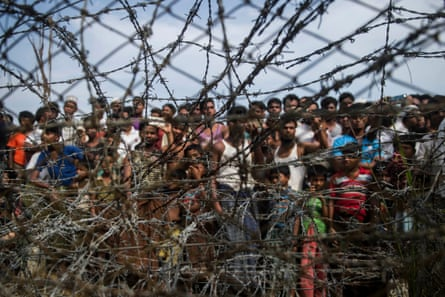 Rohingya refugees gather behind a barbed wire fence in a border zone between Myanmar and Bangladesh
