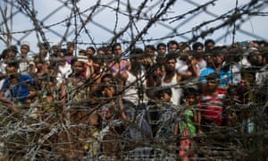 "Rohingya refugees gather behind a barbed-wire fence in a temporary settlement in a ""no man's land"" border zone between Myanmar and Bangladesh, April 2018"