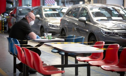 A man in a face mask taking a break at a partly taped-off rest area in front of a line of Vauxhall cars.