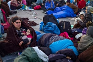 Syrian refugees rest on the ground after spending the night on Austrian-Hungarian border