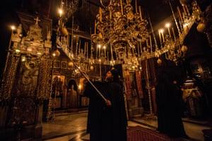 Ένας μοναχός φωτίζει τα κεριά κατά τη διάρκεια μιας επαγρύπνησης των μεσάνυχτων.  Οι μοναχοί προσεύχονται συνήθως τις πρώτες πρωινές ώρες καθώς πιστεύουν ότι αυτό είναι όταν είναι πιο κοντά στον Θεό και οι προσευχές τους ακούγονται.