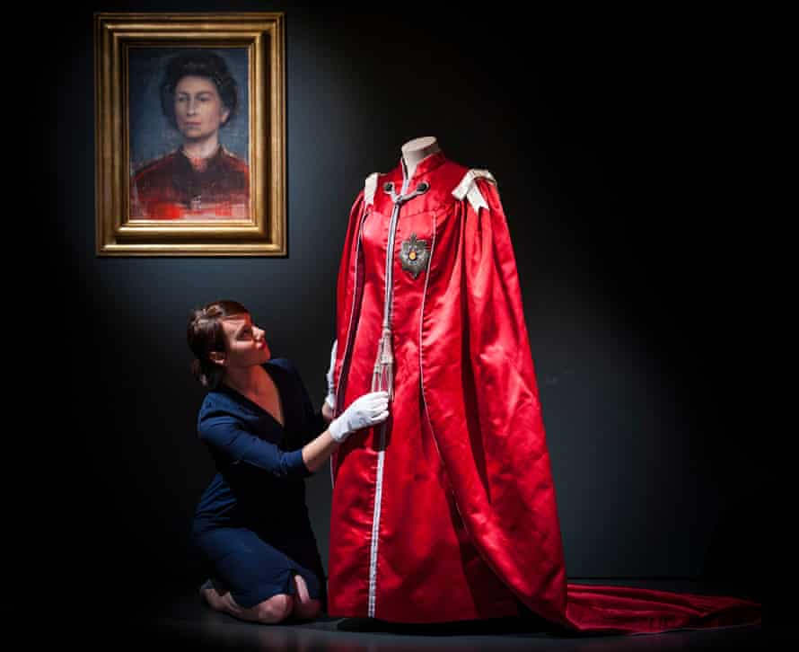 A member of staff adjusts Queen Elizabeth II's, mantle of the Order of the British Empire worn in 1952 and designed by British fashion designer Marion Foale.