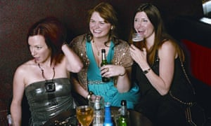 A scene from Pulling with the three women flatmates in a pub, laughing and drinking