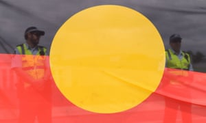 Policemen are seen standing behind an Aboriginal flag during a protest outside Parliament House in Canberra, Monday, Feb. 9, 2015. (AAP Image/Lukas Coch) NO ARCHIVING ozstock