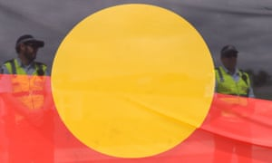 Police officers behind an Aboriginal flag