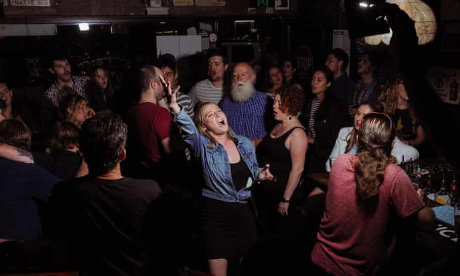 Emma Norton sings in the center of a crowd