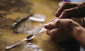 Person preparing syringe of crack cocaine.