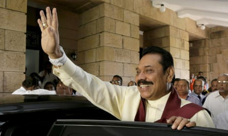 Defeated Sri Lankan president Mahinda Rajapaksa waves to his staff before leaving his office following election results in Colombo, Sri Lanka, Wednesday, Jan. 9, 2015.