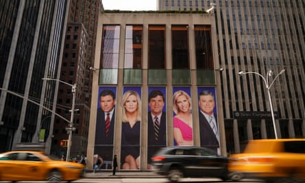 Traffic on Sixth Avenue, NY passes by ads featuring Fox News personalities, including Bret Baier, Martha MacCallum, Tucker Carlson, Laura Ingraham, and Sean Hannity, on the front of the News Corporation building.