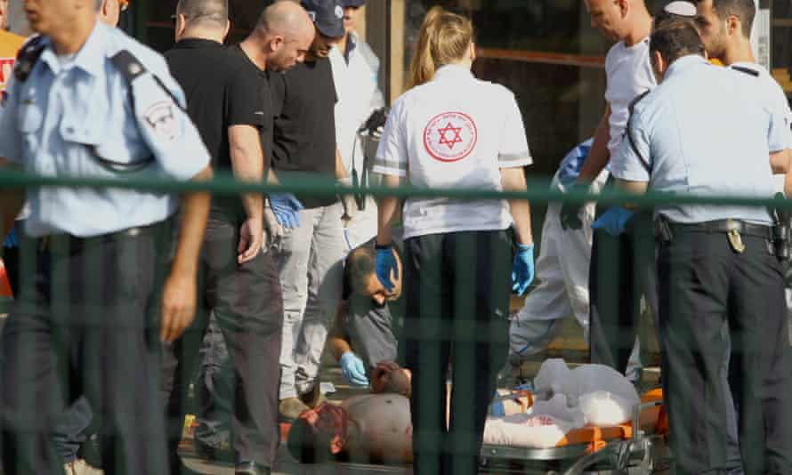 Israeli security forces stand next to a wounded and handcuffed Palestinian man who carried out a stabbing in Ra'anana