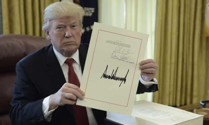 Donald Trump signs Republican tax cuts into law.