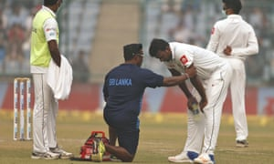 A paramedic speaks to Sri Lanka's Lahiru Gamage after he complained of shortness of breath.