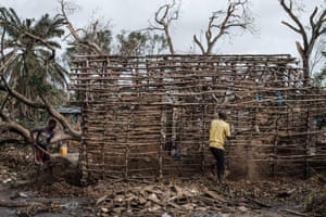 Men remove the remnants of a mud wall as they repair a house that was destroyed in Beira