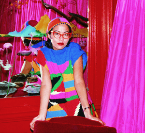 Jenny Kee in Kee knit, posing at Flamingo Park Frock Salon in 1976