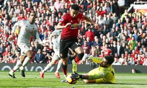 Alisson prevents a shot from Jesse Lingard.