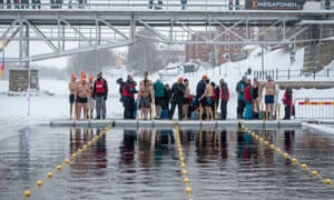 Swimmers line up at the edge of an ice pool in winter, in Skellefteå, Sweden