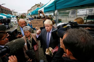 Truro, UKFormer London Mayor Boris Johnson speaks to media, whilst a protester holds up a sign, during the launch of the Vote Leave bus campaign