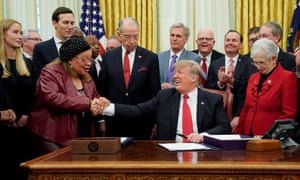Donald Trump shakes hands with Alveda King during a signing ceremony for the First Step Act at the White House on 21 December.