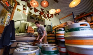 A brewer labels casks of Effra Ale at Brixton Brewery