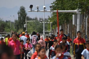 Schoolchildren walking below surveillance cameras in Akto in China's Xinjiang region.