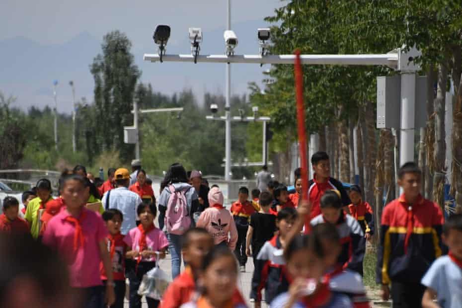 Schoolchildren walking below surveillance cameras in Akto in China's Xinjiang region.