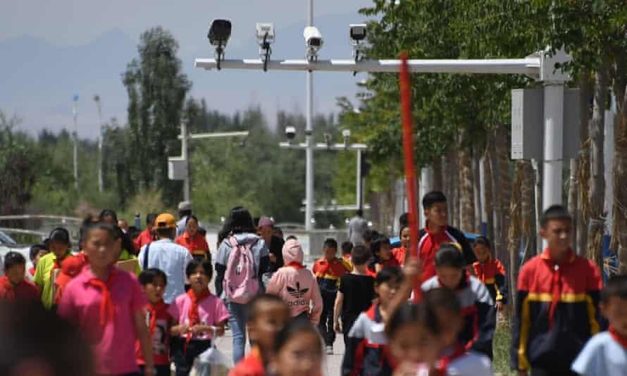 Schoolchildren walking below surveillance cameras in Akto, south of Kashgar, in China's western Xinjiang region