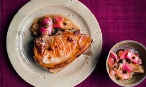 Pork chop with rhubarb chutney on a plate next to a small bowl of rhubarb chutney